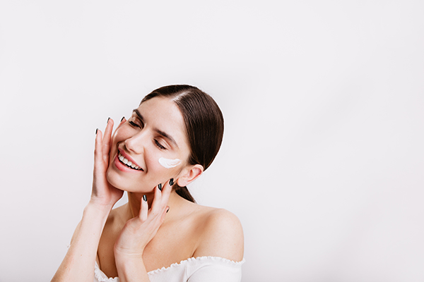 adult woman in white top cares for skin of face, applying cream. portrait of girl with ponytail on isolated background.
