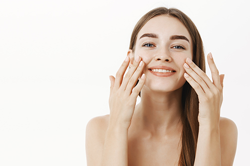 waist up shot of charming relaxed and gentle young woman making cosmetological procedure applying facial cream on face with fingers and smiling broadly feeling perfect, taking care of skin