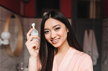 charming woman in light silk dressing gown is holding jar of face serum and smiling.